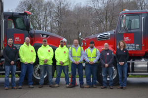 L&W Supply associates standing in front of two trucks