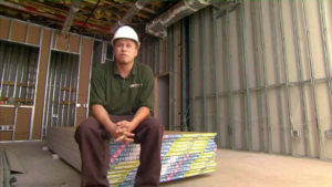 Construction worker sitting on a stack of drywall