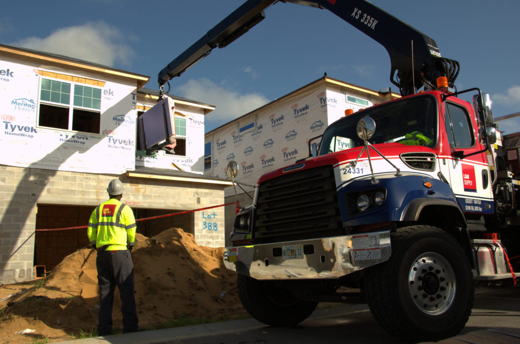 An L&W Supply truck making a delivery to a jobsite
