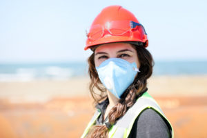 Occupational health and safety (OHS) woman staff (engineer) looking at the camera with protective mask for coronavirus (covid-19) in the construction field.