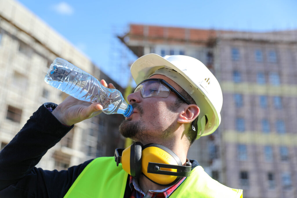 Worker at construction site on a hot day hydrating